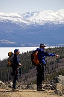 Group of hikers, man and woman hiking, backpacks, ice covered Kusawa Lake behind, Yukon Territory, Canada, North America