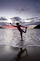 Young woman doing yoga at the beach during sunset in Playas del Coco, Costa Rica