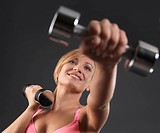 Smiling young fitness woman exercising with weights