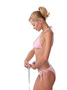 Young slim woman measuring her waist with a tape measure