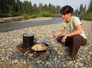 Young woman cooking, frying chicken stir fry on a camp fire, gravel bar, upper Liard River, Yukon Territory, Canada