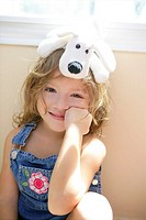 Happy toddler blond girl with toy dog over head