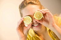 Teenage girl covering her eyes with slices of lemon