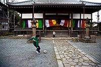 Japanese children playing soccer in a temple in Hita Japan