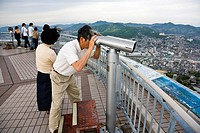 Man using binoculars seeing Nagasaki from a viewpoint