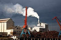 Cranes and scrap and a smoking chimney in a Port.Rio Nervion, Bilbao,Vizcaya,Basque Country,Spain