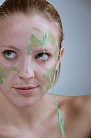 Young woman peeling off a facial mask