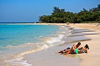 Cuban teenage couple laying on a sandy beach by the ocean