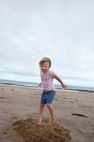 Happy 5 year blonde girl jumping for joy on beach