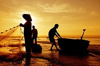 Silhouetted fishermen on Mui Ne Beach in Vietnam