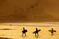Three surfers leave the water at sunset on Las Canteras Beach