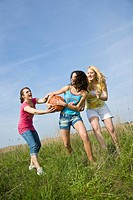 Three girls playing with a basketball on a meadow