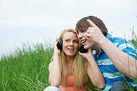 Young couple sitting on a lawn, listening to music with headphones