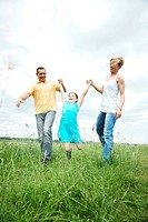 Happy family walking across a meadow
