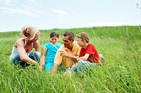 Family sitting on a meadow