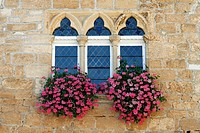 Paladian windows with flowers Domme fortress Dordogne Aquitaine France travel tourist destination hilltown