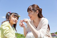 Japan, Tokyo Prefecture, Mother and daughter looking at flower, smiling