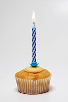 Cup cake with blue candle in it