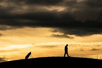Golfer at sunset, walking to his ball  Moody clouds rolling in during an atmospheric game of golf