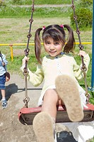 Japan, Tokyo Prefecture, Children swinging, portrait