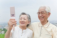 Japan, Tokyo Prefecture, Senior couple photographing with mobile phone, smiling, close_up