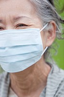 Japan, Tokyo Prefecture, Senior woman wearing flu mask, close_up