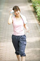 Japan, Osaka Prefecture, Woman wiping sweat with towel, smiling