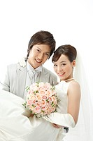 portrait of smiling bride and groom holding bouquet of flowers