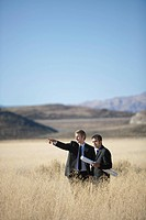 2 men with blueprints in field pointing
