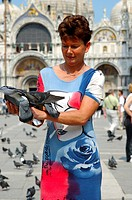 Woman with pigeons on San Marcus Square, Venice Italy