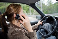 A woman phones at the steering wheel