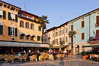 A plaza with restaurants at sunset Sirmion, e Lake Garda, Italy