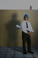 Architect carrying blueprint under arm, full length portrait