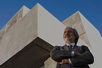Architect standing in front of building with arms folded, looking away, low angle view