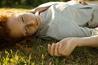 Woman lying on back in grass