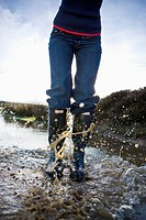 Woman in wellingtons splashing in water