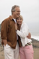 Mature couple embracing on beach (thumbnail)