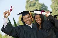 Two graduates hoisting diplomas outside portrait (thumbnail)