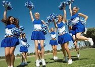 Group of Cheerleaders rising pom_poms jumping on football field