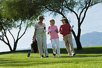 Three women walking on golf course