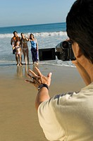 Man filming family on beach (thumbnail)