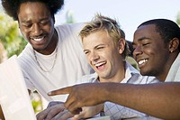 Three friends at back yard table looking at laptop laughing close up
