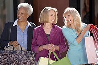 Smiling Women walking outside carrying bags on Shopping Trip (thumbnail)