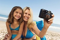 Girl and mother photographing themselves on beach