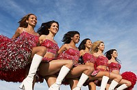 Cheerleaders in a row kicking legs
