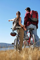 Young Couple standing with mountain bikes holding hands back view