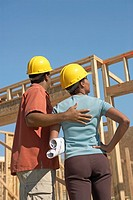 Couple in hard hats on building site back view (thumbnail)