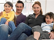 Family with two children 3-6 on couch portrait (thumbnail)