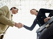 Businessman and businesswoman shaking hands low angle view