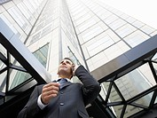 Businessman using mobile phone outside office low angle view